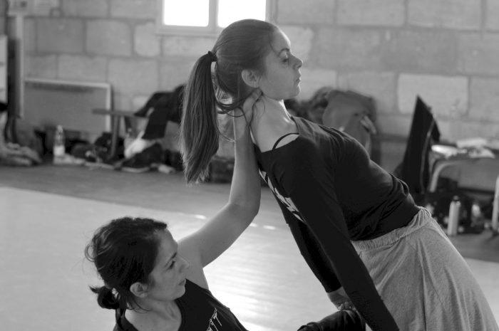 Photo illustation de l'atelier chorégraphique - 2 danseuses, l'une en appui sur le sol soutien l'autre de son bras